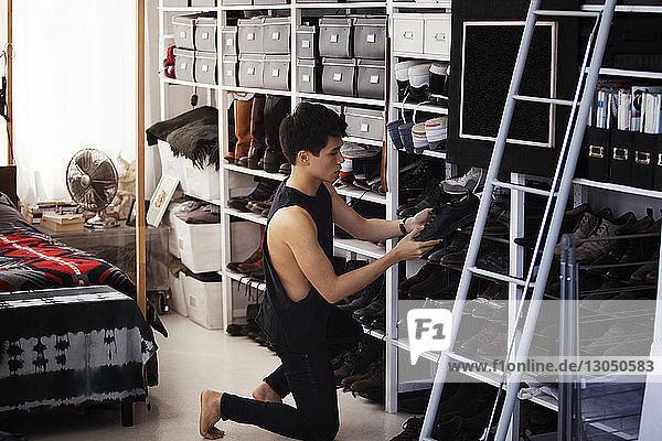 Mann entfernt Schuhe aus dem Regal im Schlafzimmer