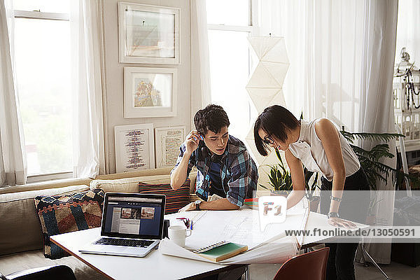 Young couple analyzing blueprint at home