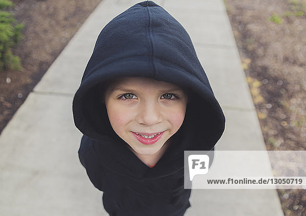 High angle portrait of happy boy wearing black hooded jacket while standing on footpath
