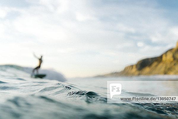 Defokussiertes Bild des Menschen  der auf dem Meer vor bewölktem Himmel surft