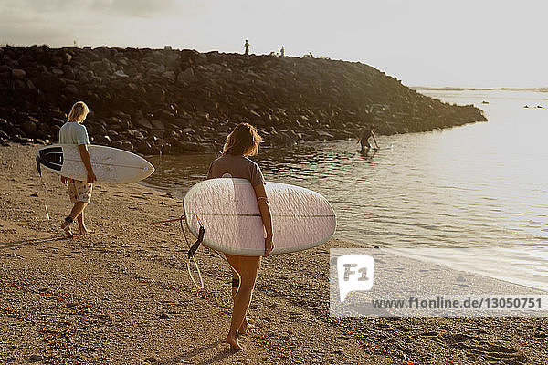 Friends with surfboards walking on shore at beach