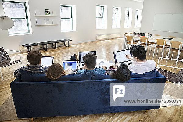 Rückansicht von Geschäftsleuten  die Laptops auf dem Sofa im Kreativbüro benutzen