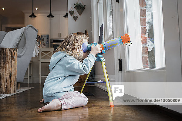 Side view of girl looking through telescope while kneeling by door at home