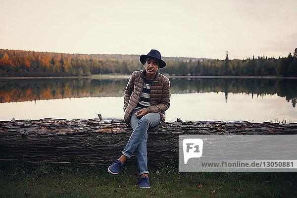 Full length portrait of man sitting on log by lake