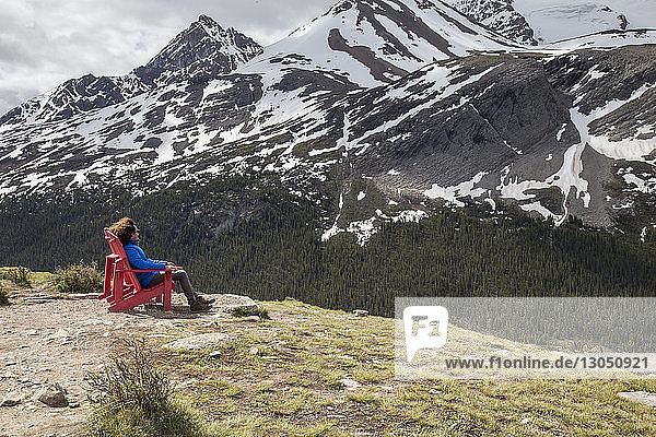 Hiker looking at view while resting on chair against mountains