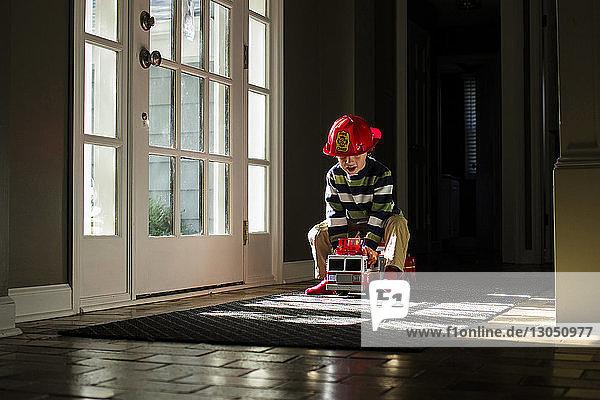 Verspielter Junge fährt zu Hause ein Spielzeug-Feuerwehrauto