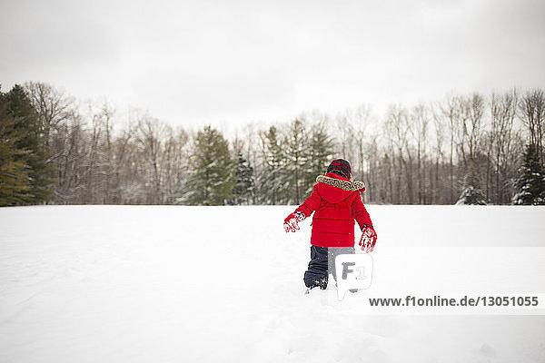 Rückansicht eines Jungen  der auf einem schneebedeckten Feld spielt