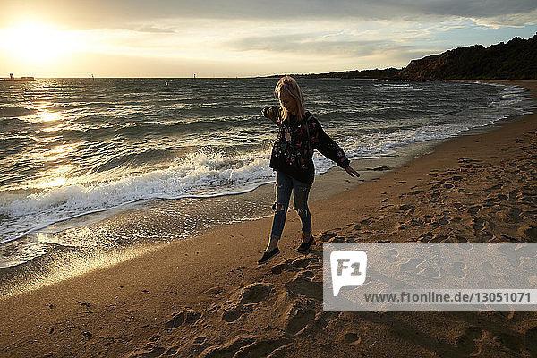 Frau in voller Länge mit ausgestreckten Armen am Strand der Half Moon Bay