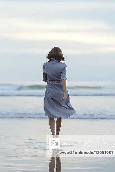 Rückansicht einer sorglosen Frau  die bei Sonnenuntergang am Strand in Richtung Meer geht