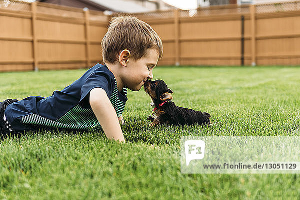 Boy kissing dog while lying on grassy field