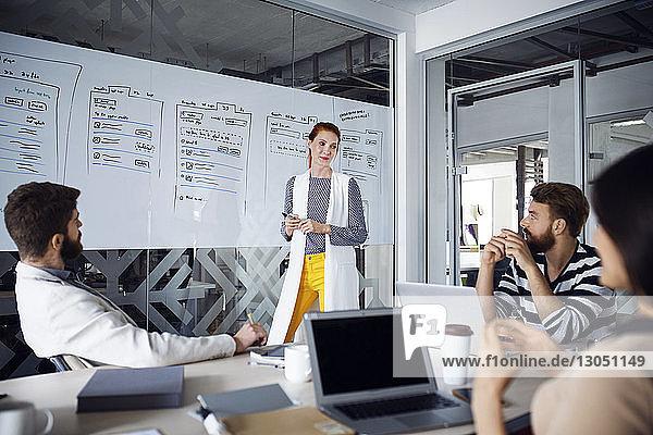 Zuversichtliche Geschäftsfrau diskutiert mit Kollegen im Sitzungssaal