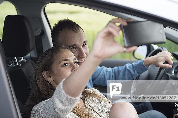 Frau nimmt sich im Urlaub mit dem Mann über Smartphone im Auto mit