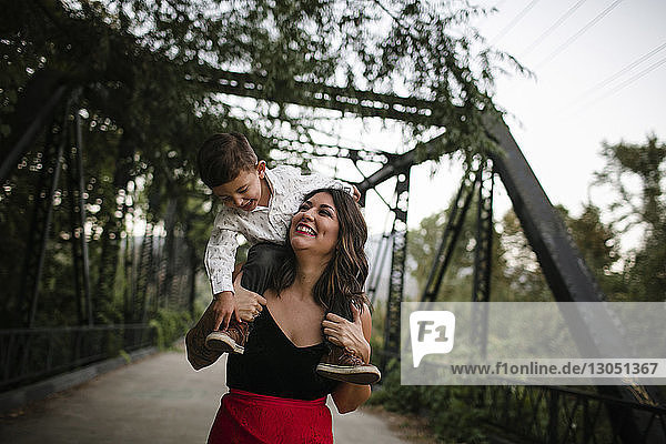 Cheerful mother carrying son on shoulders at bridge