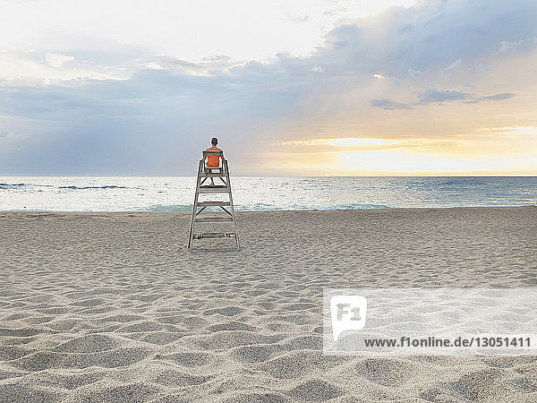 Rear view of man sitting on lifeguard hut at beach against cloudy sky during sunset