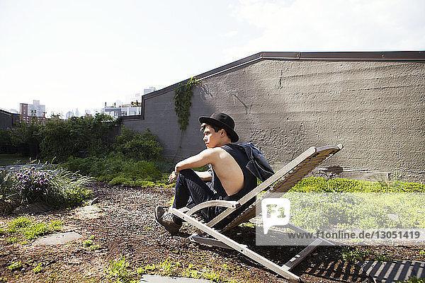 Seitenansicht eines nachdenklichen Mannes  der auf einem Liegestuhl auf der Terrasse sitzt