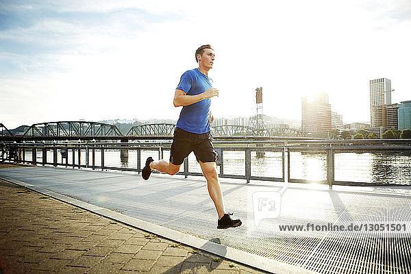 Sportlicher Mann joggt auf Promenade gegen den Himmel