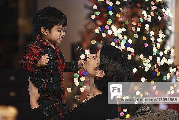 Side view of mother with son by illuminated Christmas tree at home
