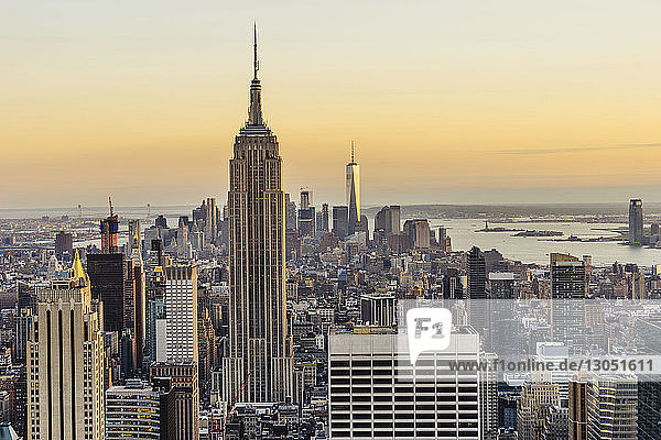 Empire State Building and One World Trade Center in city against sky during sunset