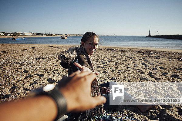 Ausgeschnittenes Bild einer Frau  die die Hand eines Mannes hält  während sie am Strand im Sand sitzt