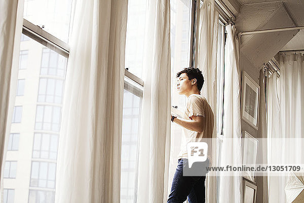 Side view of thoughtful man looking through window at home