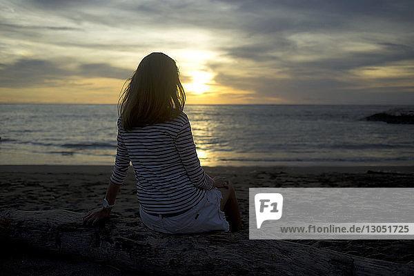 Rückansicht einer Frau  die sich bei Sonnenuntergang am Meer vor bewölktem Himmel entspannt