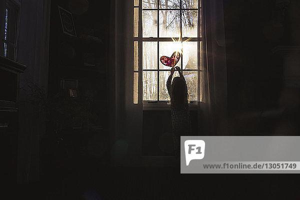Rear view of playful girl making heart shape on window