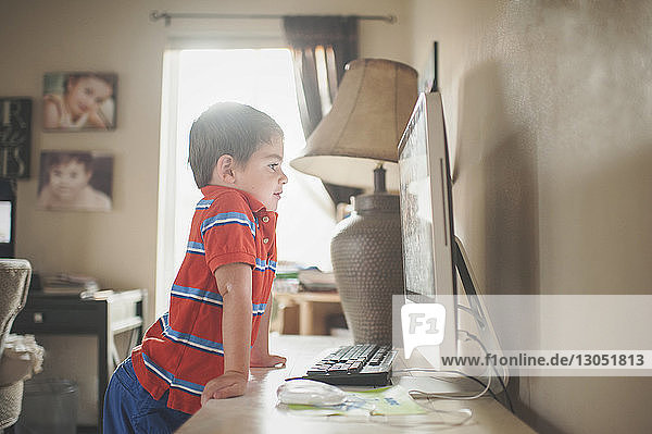 Boy looking at desktop computer while standing by table at home