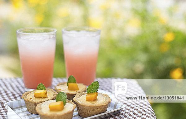 Hochwinkelansicht von Torten mit Getränken auf dem Tisch gegen Pflanzen