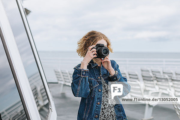 Young woman taking photographs on pier  Menemsha  Martha's Vineyard  Massachusetts  USA