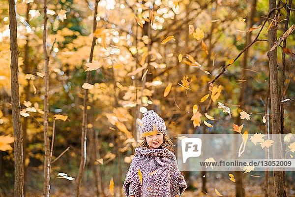 Fallendes Herbstlaub vor einem kleinen Mädchen im Wald