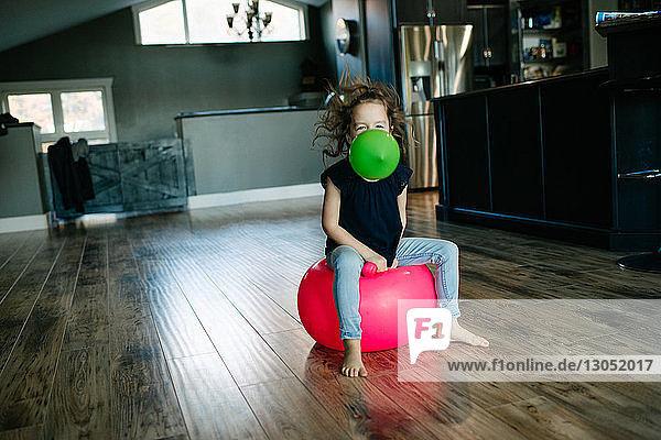 Kleines Mädchen mit Luftballon im Mund hüpft zu Hause auf dem Gymnastikball