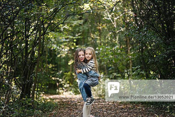Schwestern umarmen sich im Wald