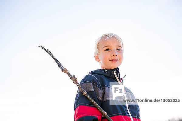 Junge mit Stock gegen klaren weißen Himmel