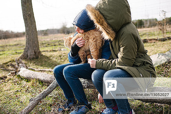 Brother and sister cuddling cat in field