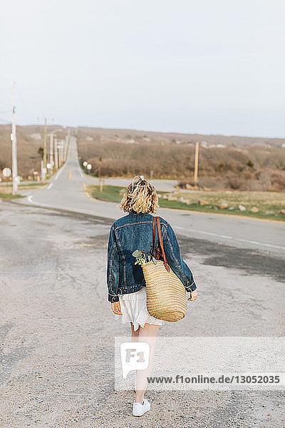 Young woman walking toward rural road  rear view  Menemsha  Martha's Vineyard  Massachusetts  USA