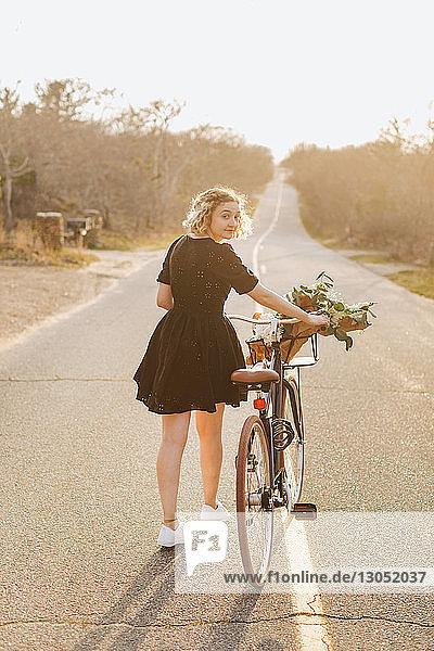 Junge Frau schiebt Fahrrad auf ländlicher Strasse  Rückansicht Porträt  Menemsha  Martha's Vineyard  Massachusetts  USA