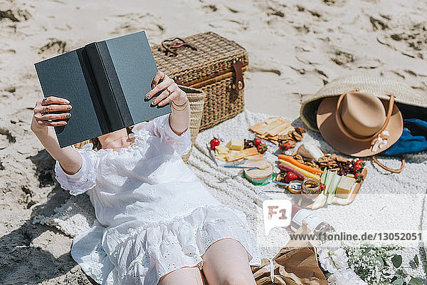 Young woman on picnic blanket at beach reading book  Menemsha  Martha's Vineyard  Massachusetts  USA