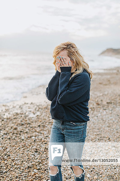 Young woman covering her face with hands on beach  Menemsha  Martha's Vineyard  Massachusetts  USA