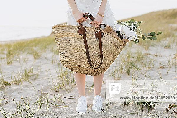 Young woman carrying shoulder bag with flowers on coastal dunes  waist down  Menemsha  Martha's Vineyard  Massachusetts  USA
