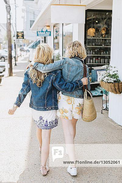 Two young female friends strolling along village sidewalk  rear view  Menemsha  Martha's Vineyard  Massachusetts  USA