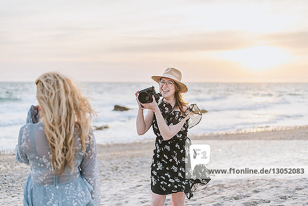 Young woman photographing friend on windy beach  Menemsha  Martha's Vineyard  Massachusetts  USA