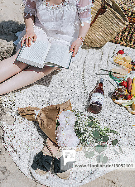 Young woman reading book on beach  mid section  Menemsha  Martha's Vineyard  Massachusetts  USA