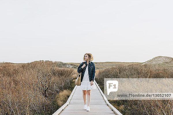 Lone young woman strolling on coastal dune boardwalk  Menemsha  Martha's Vineyard  Massachusetts  USA
