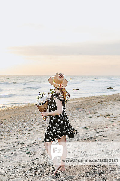 Junge Frau mit Blumenstrauss am windigen Strand,  Menemsha,  Martha's Vineyard,  Massachusetts,  USA