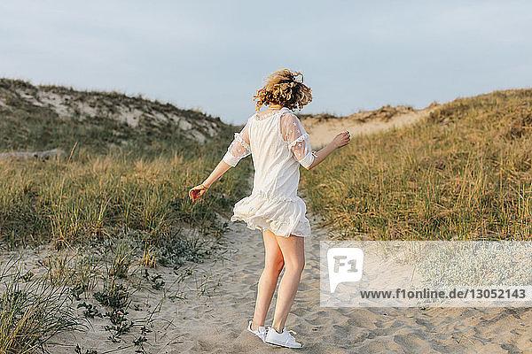 Junge Frau in weißem Kleid tanzt auf Küstendünen  Menemsha  Martha's Vineyard  Massachusetts  USA