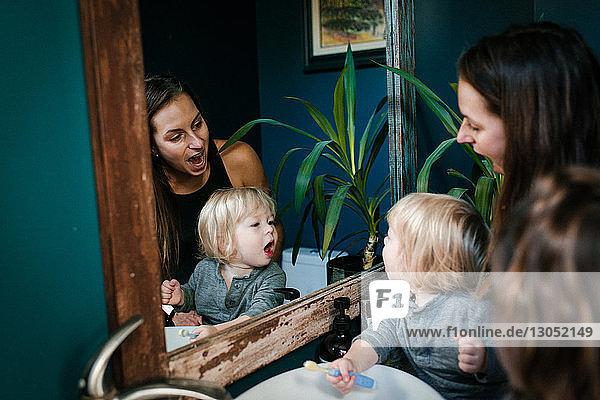 Mutter und Sohn schauen mit offenem Mund in den Spiegel