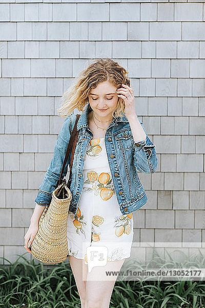 Junge Frau mit Strohsack vor der Wand