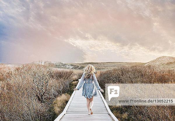Barefoot young woman strolling on coastal dune boardwalk  rear view  Menemsha  Martha's Vineyard  Massachusetts  USA