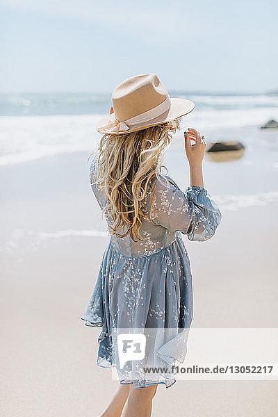 Young woman on windy beach  rear view  Menemsha  Martha's Vineyard  Massachusetts  USA