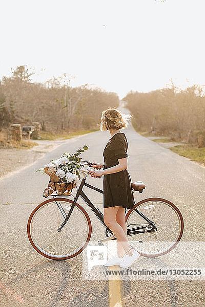 Junge Frau mit Fahrrad  die seitlich auf die Landstraße schaut  Menemsha  Martha's Vineyard  Massachusetts  USA